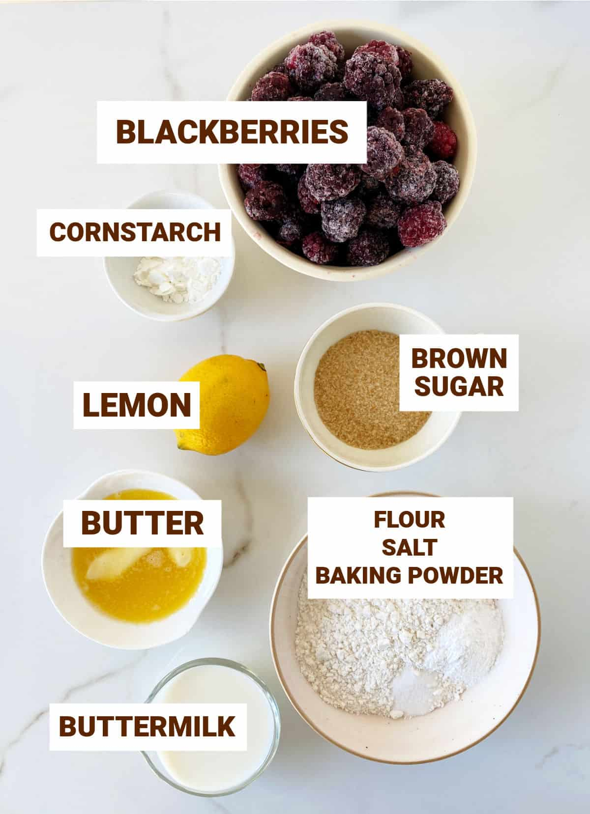 White surface with bowls containing blackberry cobbler ingredients including lemon, brown sugar, butter, dry mixture