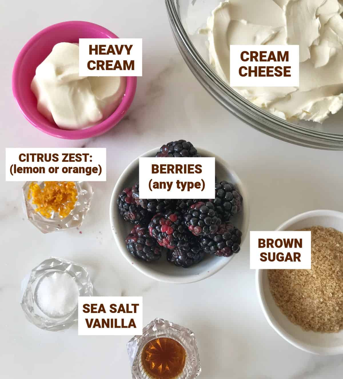 Ingredients for cheesecake berry ice cream in bowls on white surface including berries, cream, brown sugar, zest