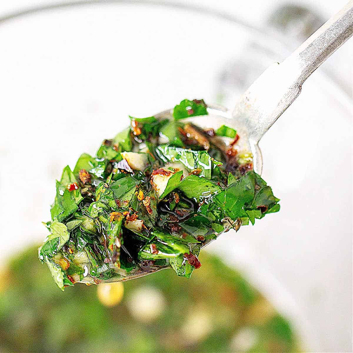 Close up of spoon with chimichurri sauce, glass jar with more sauce below