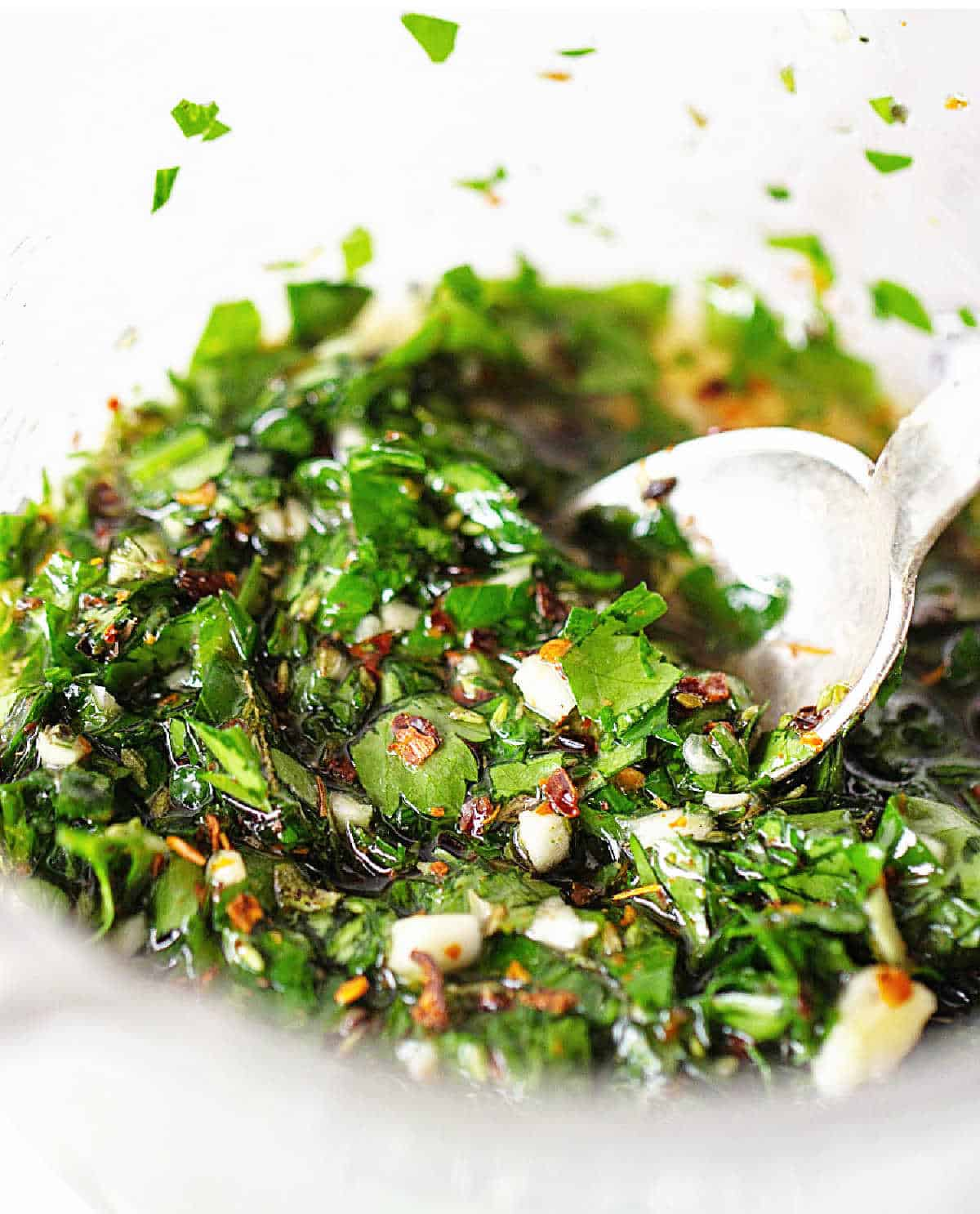 A glass jar with chimichurri sauce, a silver spoon, close up image