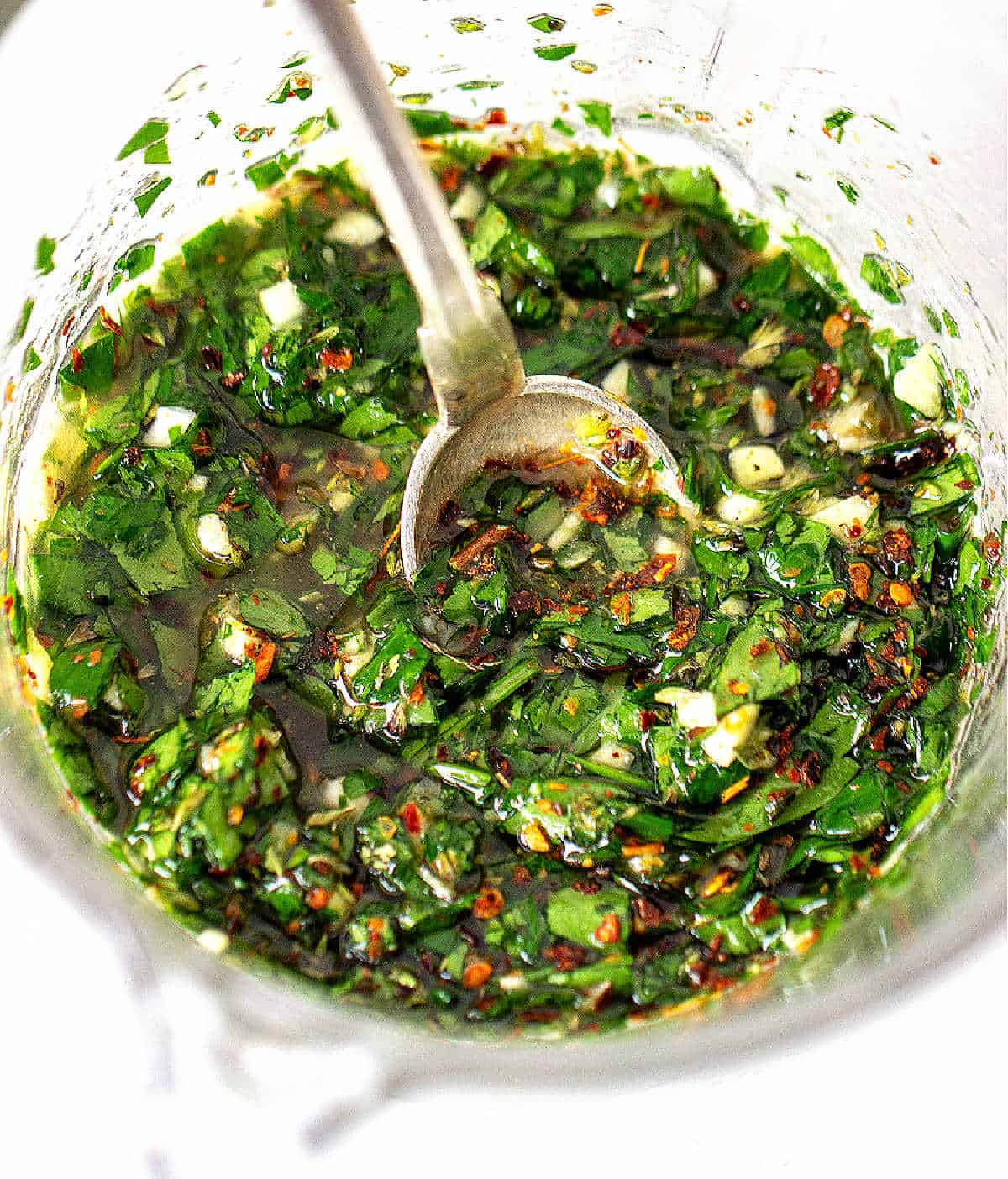 Silver spoon inside green chimichurri sauce in glass container, white surface