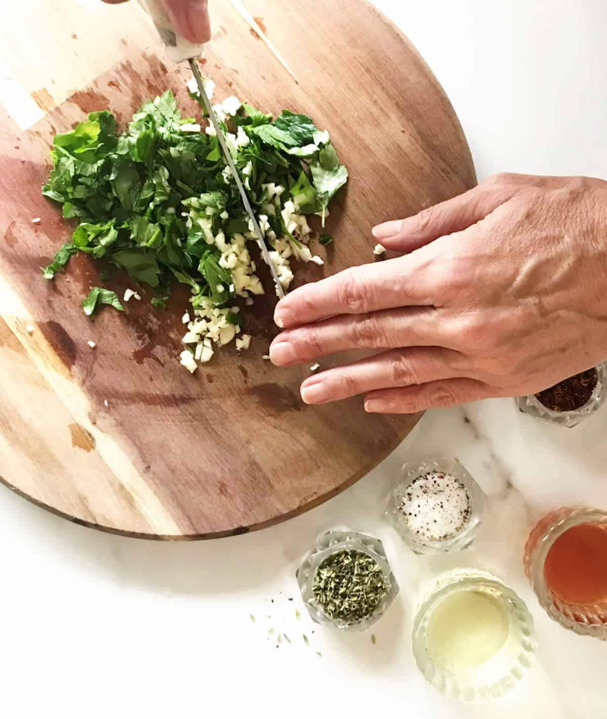 Hands chopping parlesy and garlic on wooden board, white table with more ingredients