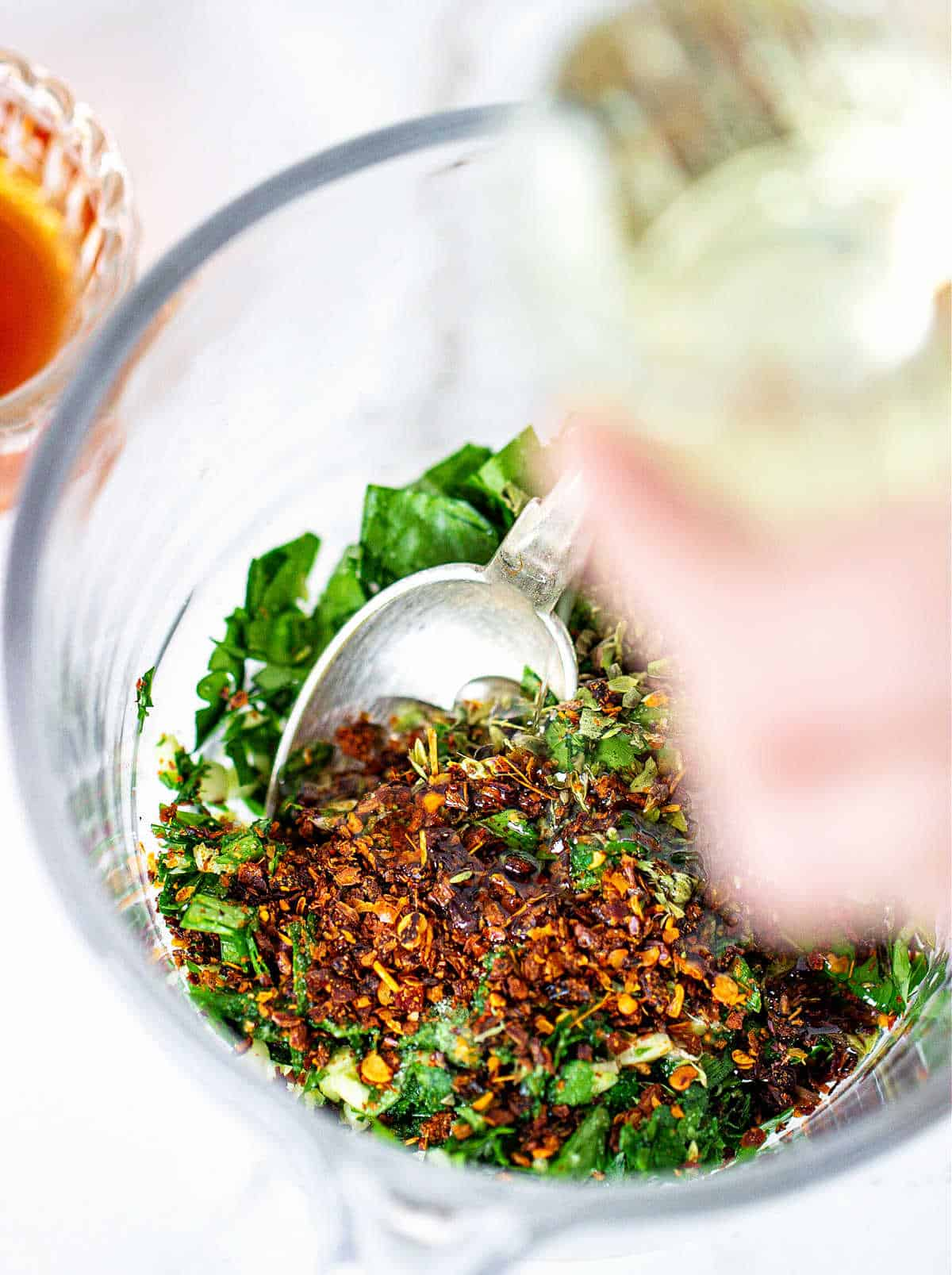 Adding oil to chimichurri ingredients in a glass jar