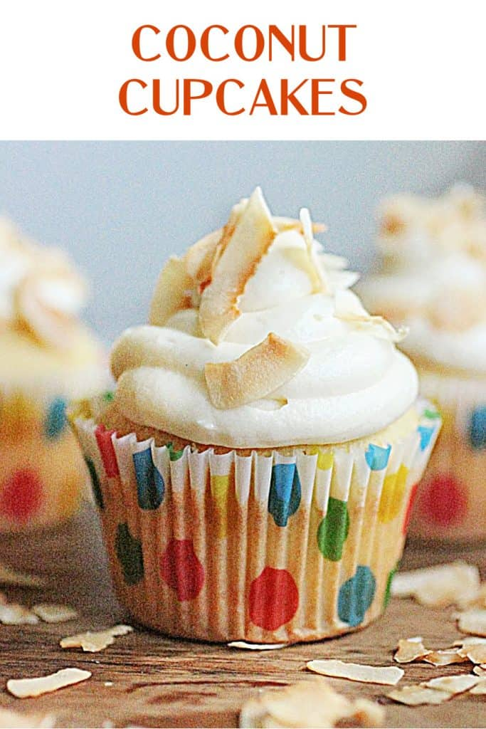 Cream cheese frosted cupcakes in dotted paper liners, wooden table, bluish background