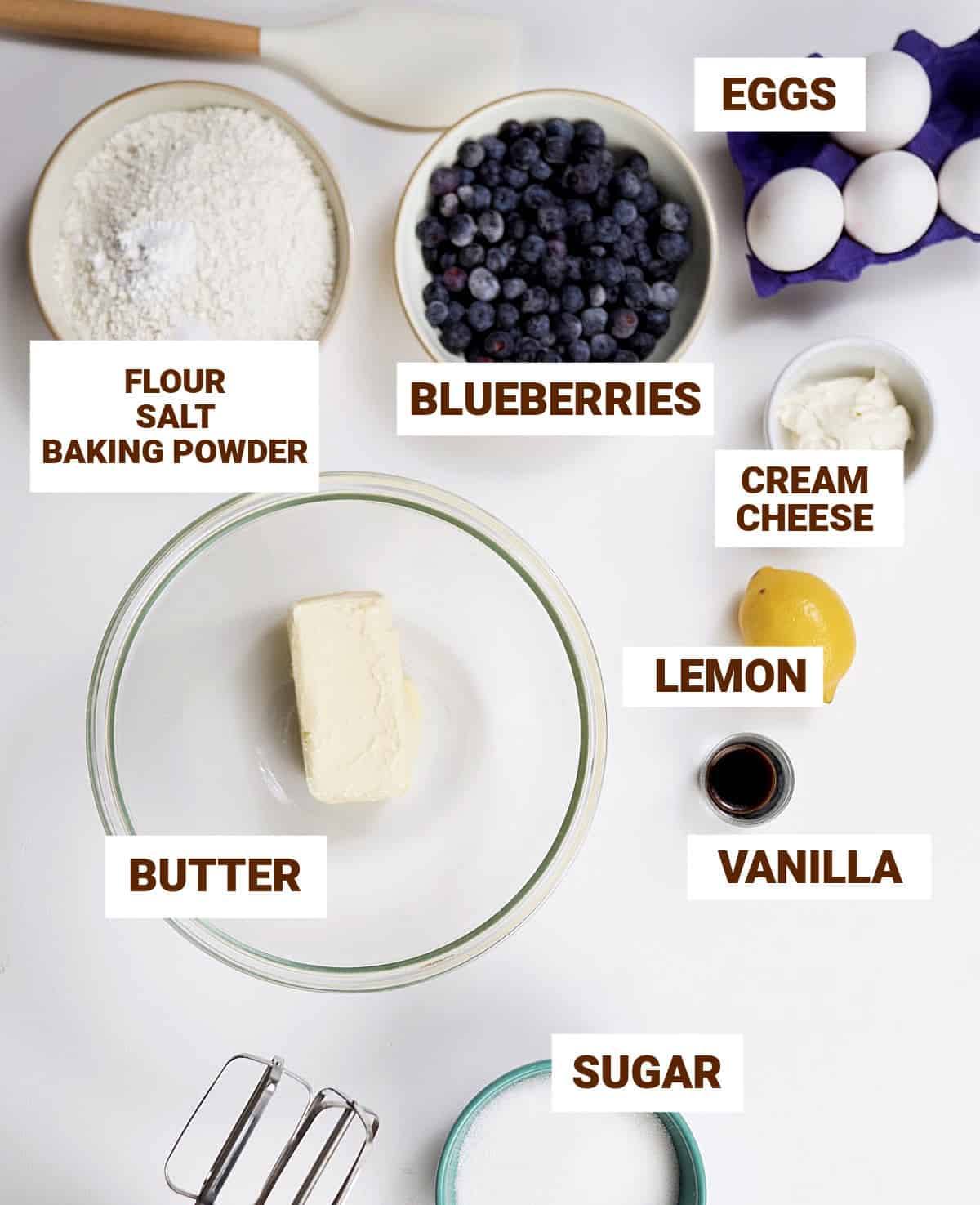 White surface with bowls containing lemon blueberry cake ingredients including butter, vanilla, flour mixture, sugar