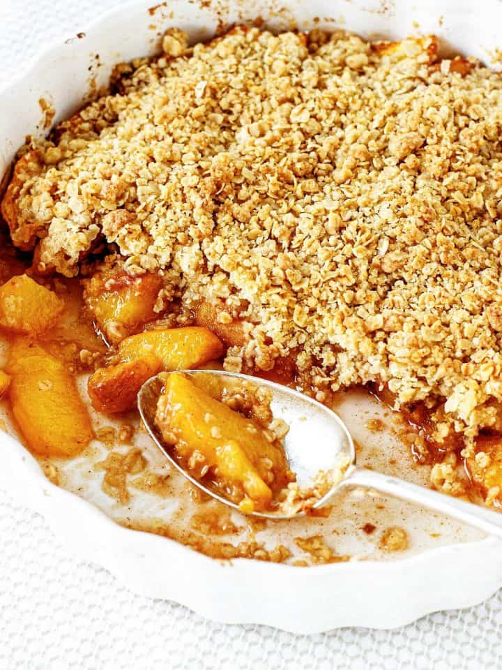 White round dish with peach crisp and silver spoon