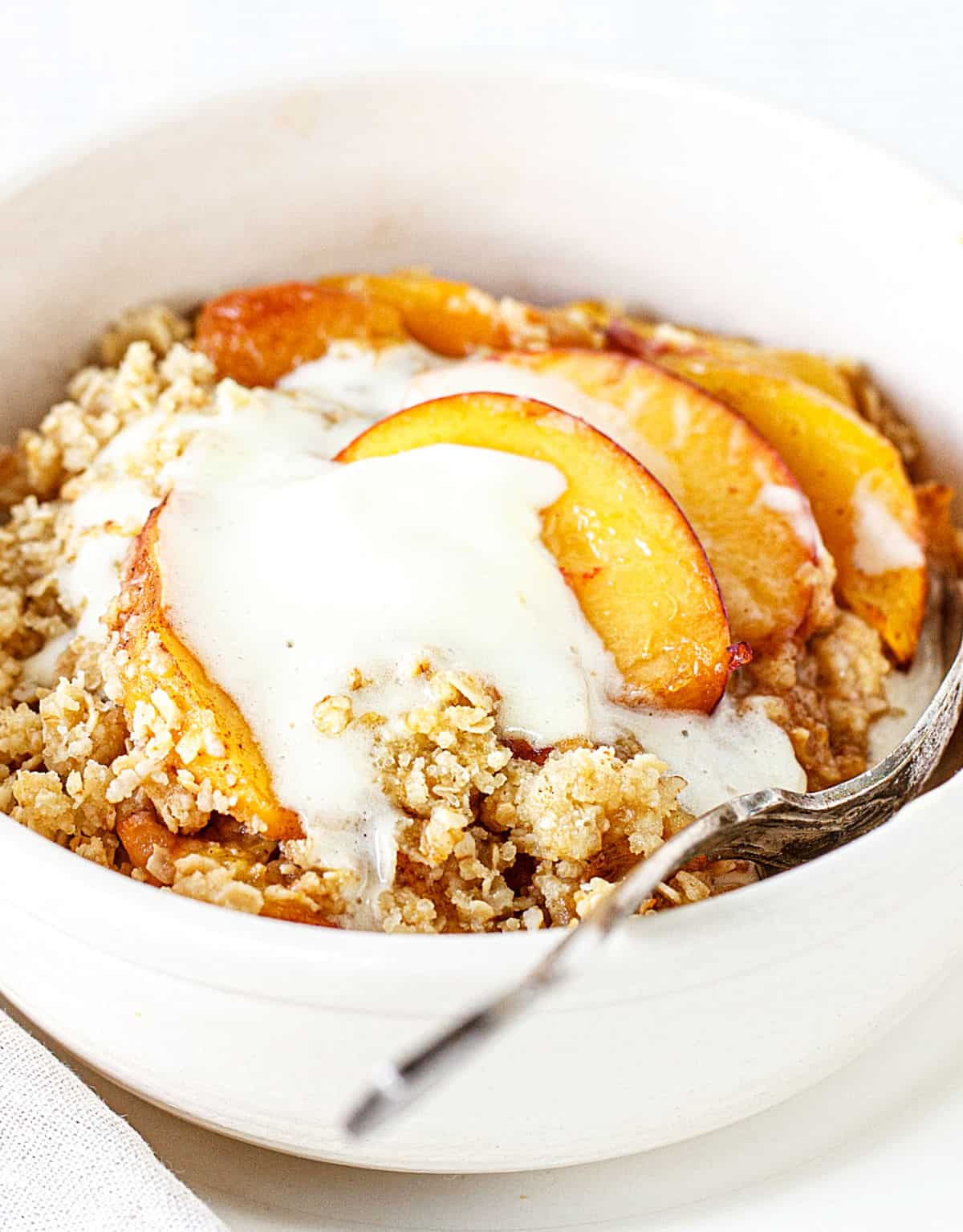 Peach crisp serving with ice cream in white bowl with a silver spoon