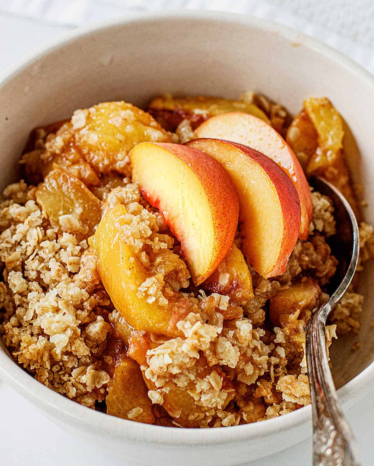 White bowl with peach crisp serving and silver spoon inside