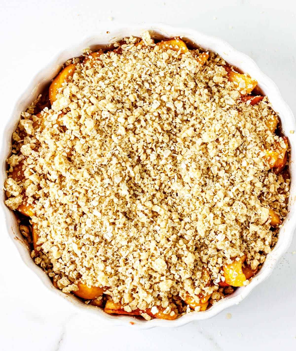 Round dish with unbaked peach crisp on white surface