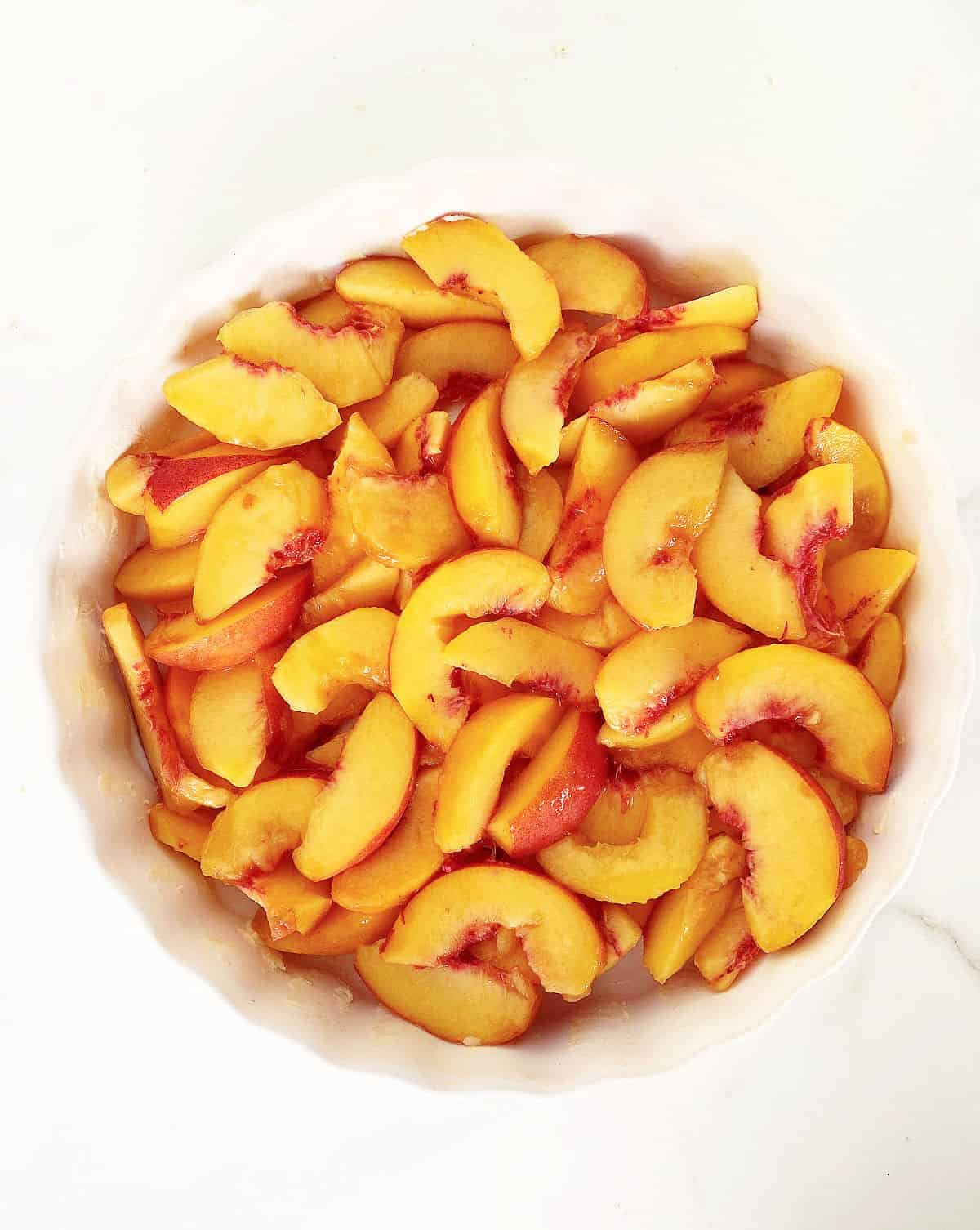 Top view of sliced peaches in white round dish, white surface