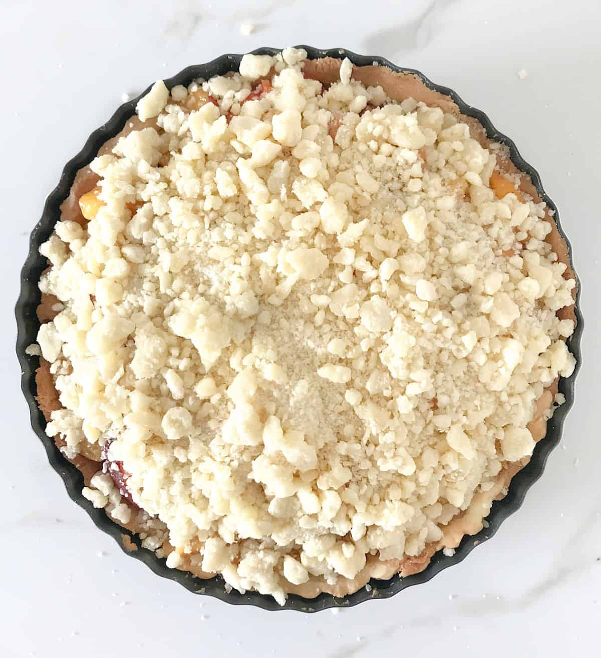 Top view of round pan with unbaked crumb pie on white marble