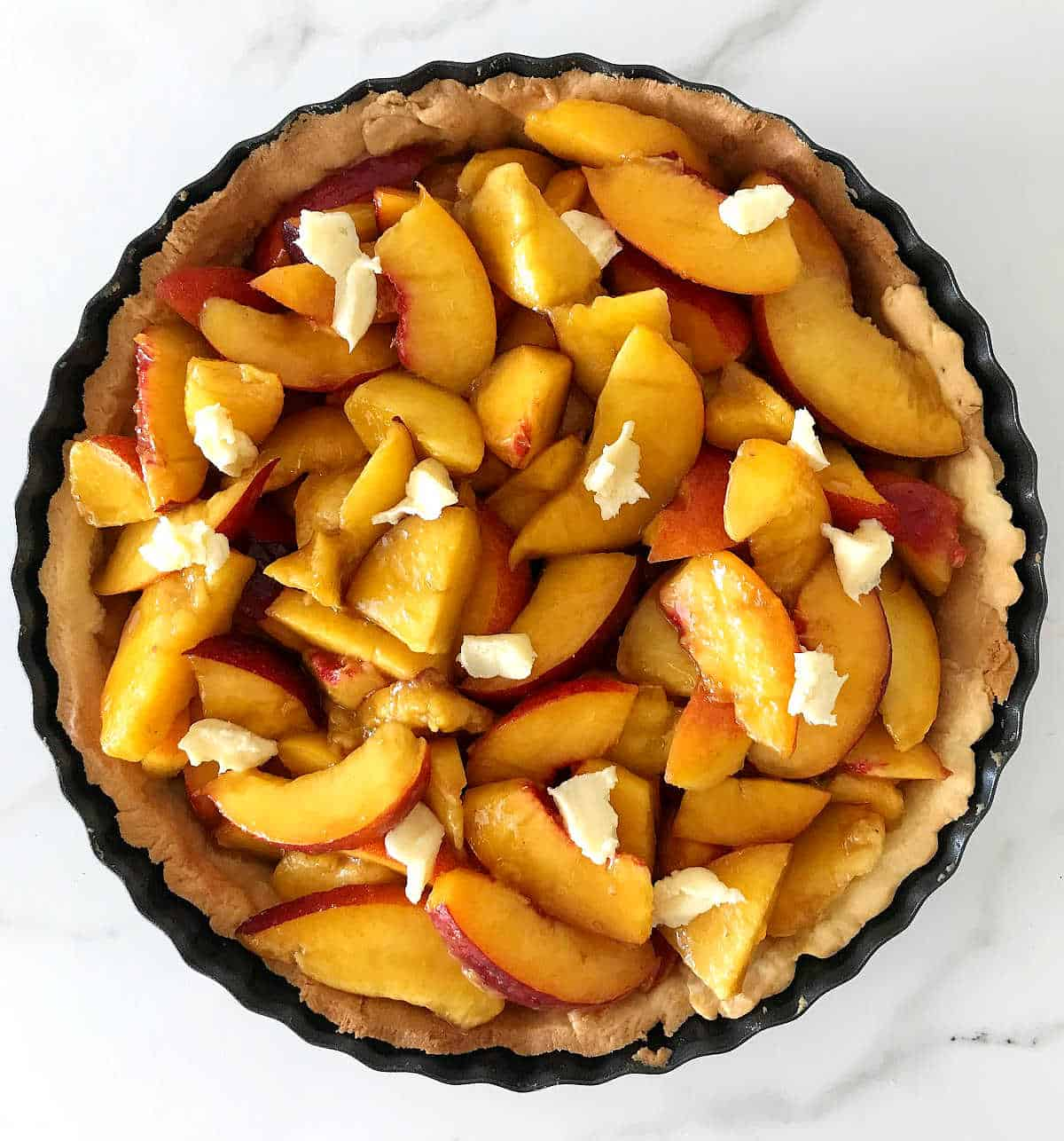 Unbaked pie peach filling in pie shell on white surface