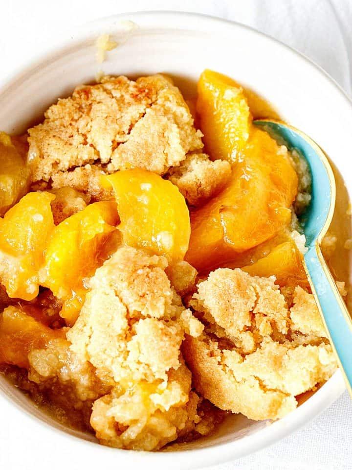 A white bowl with peach dump cake, blue spoon
