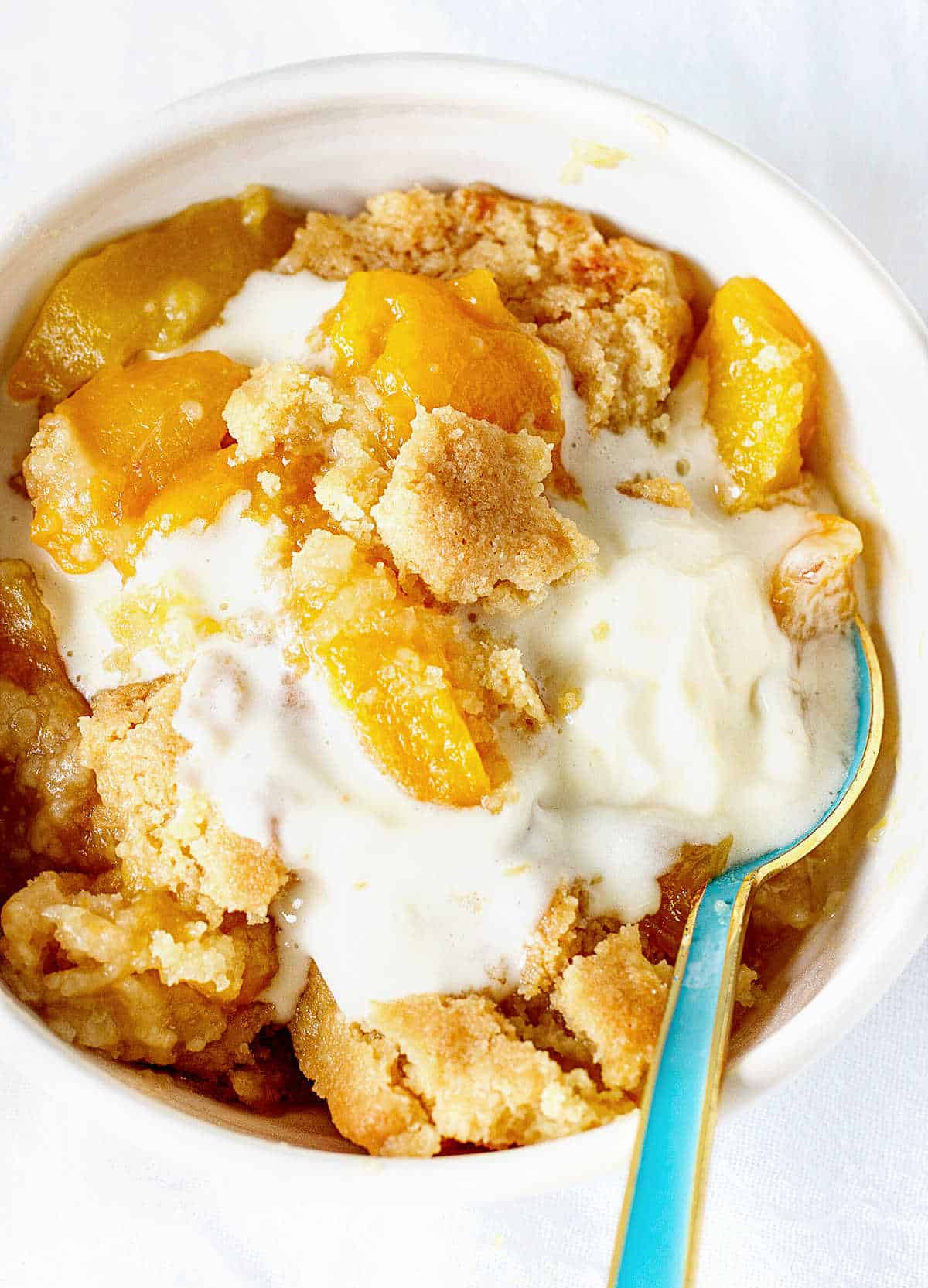 Overview of white bowl with peach dump cake and ice cream, greenish spoon