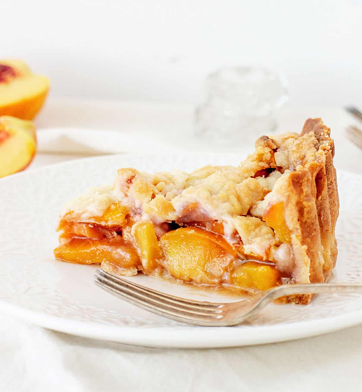 Slice of peach crumb pie on white plate, white background