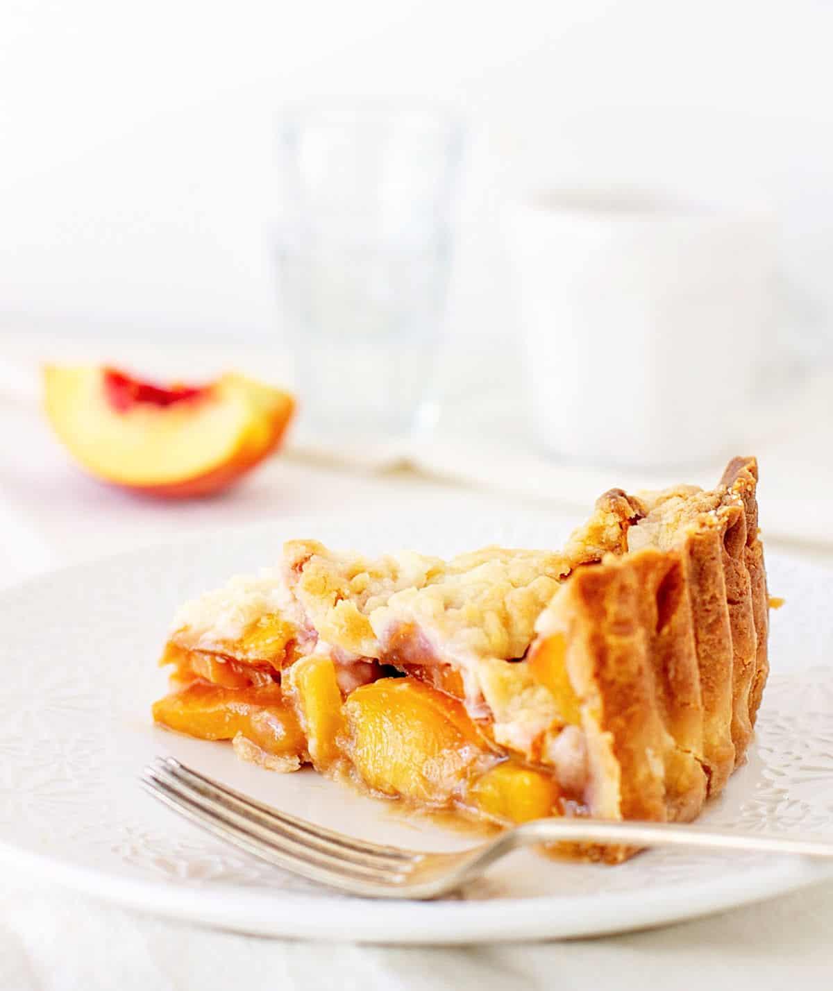 Peach pie slice on white plate, silver fork, white background, peach wedge