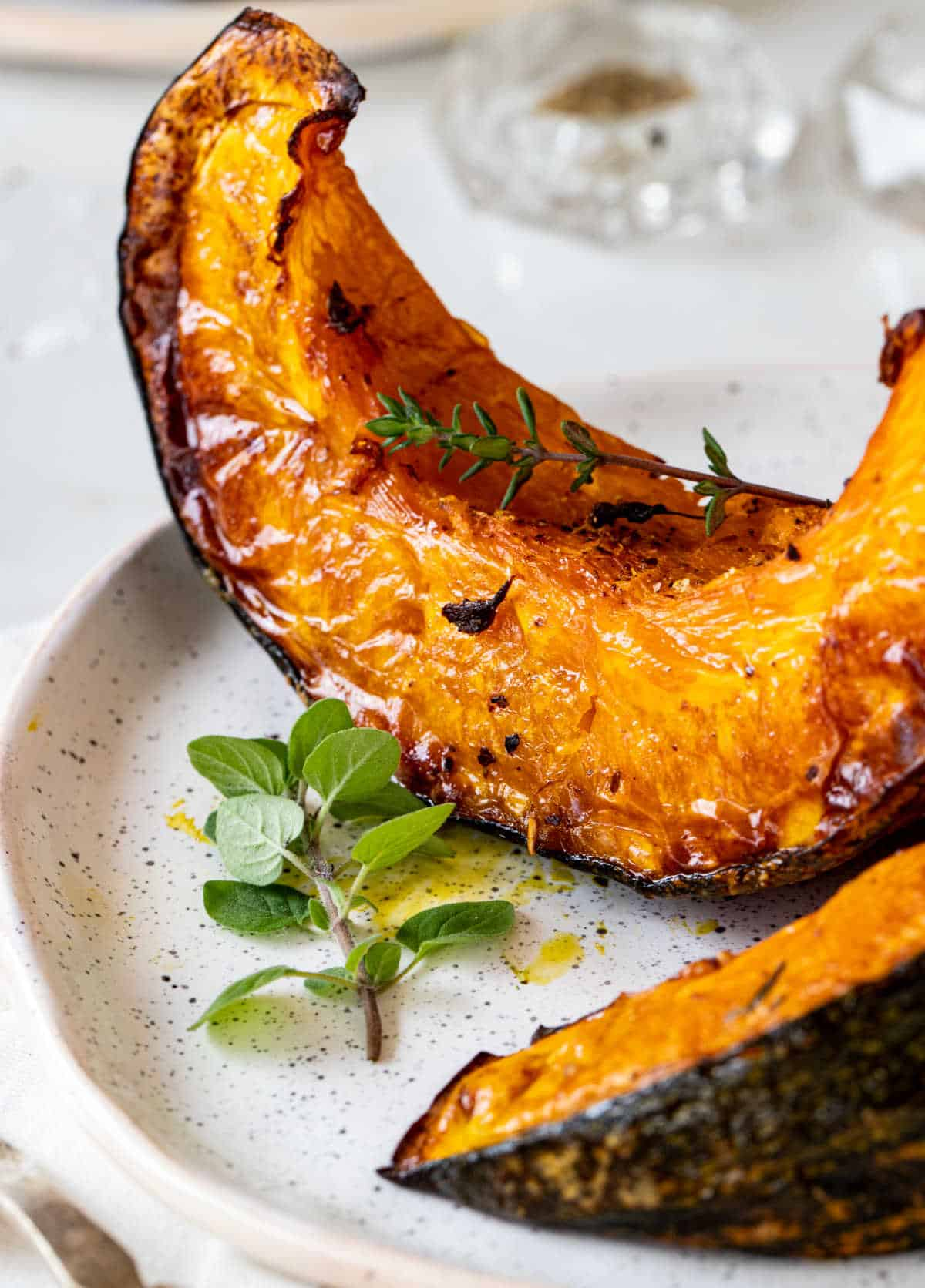 Close up of partial roasted pumpkin wedges on white plate, fresh herbs