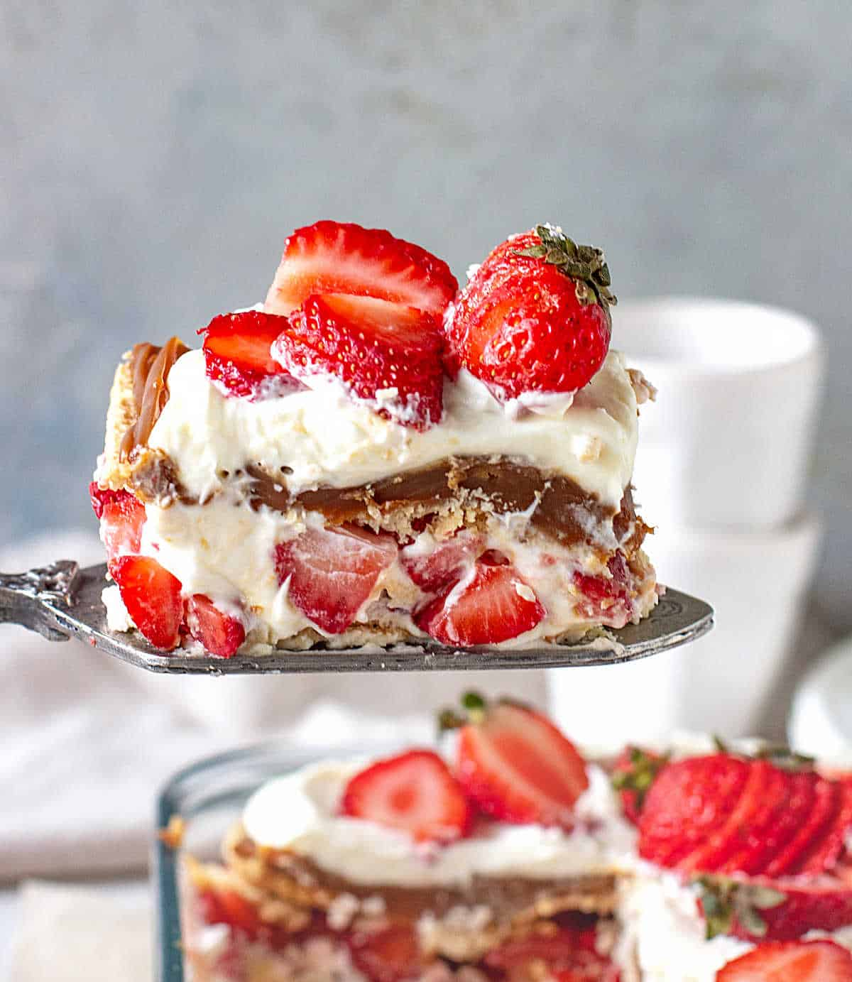 Lifting a slice of no-bake strawberry cake with an antique cake server, dessert dish beneath it