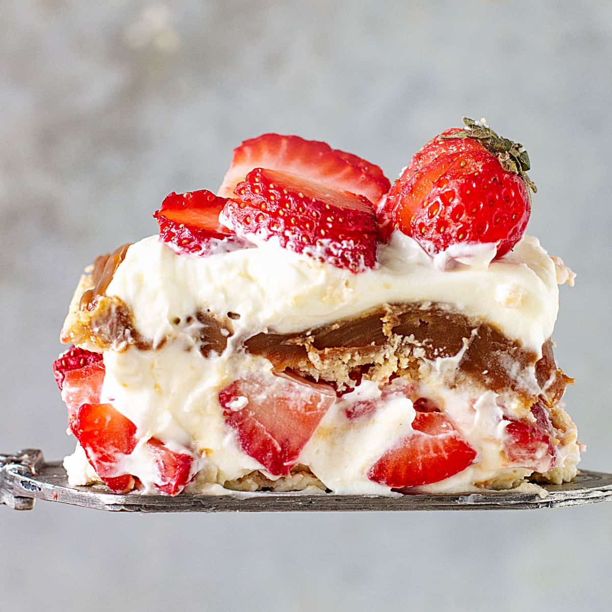 Close up of strawberry icebox cake serving on silver cake server, grey background