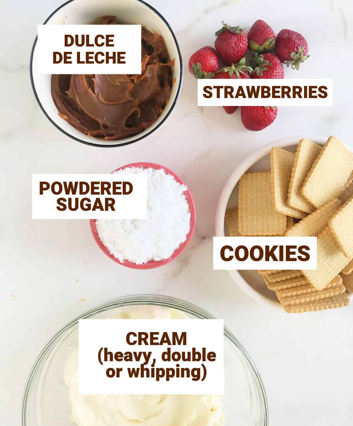Bowls with strawberries, cookies, cream and other ingredients on white surface