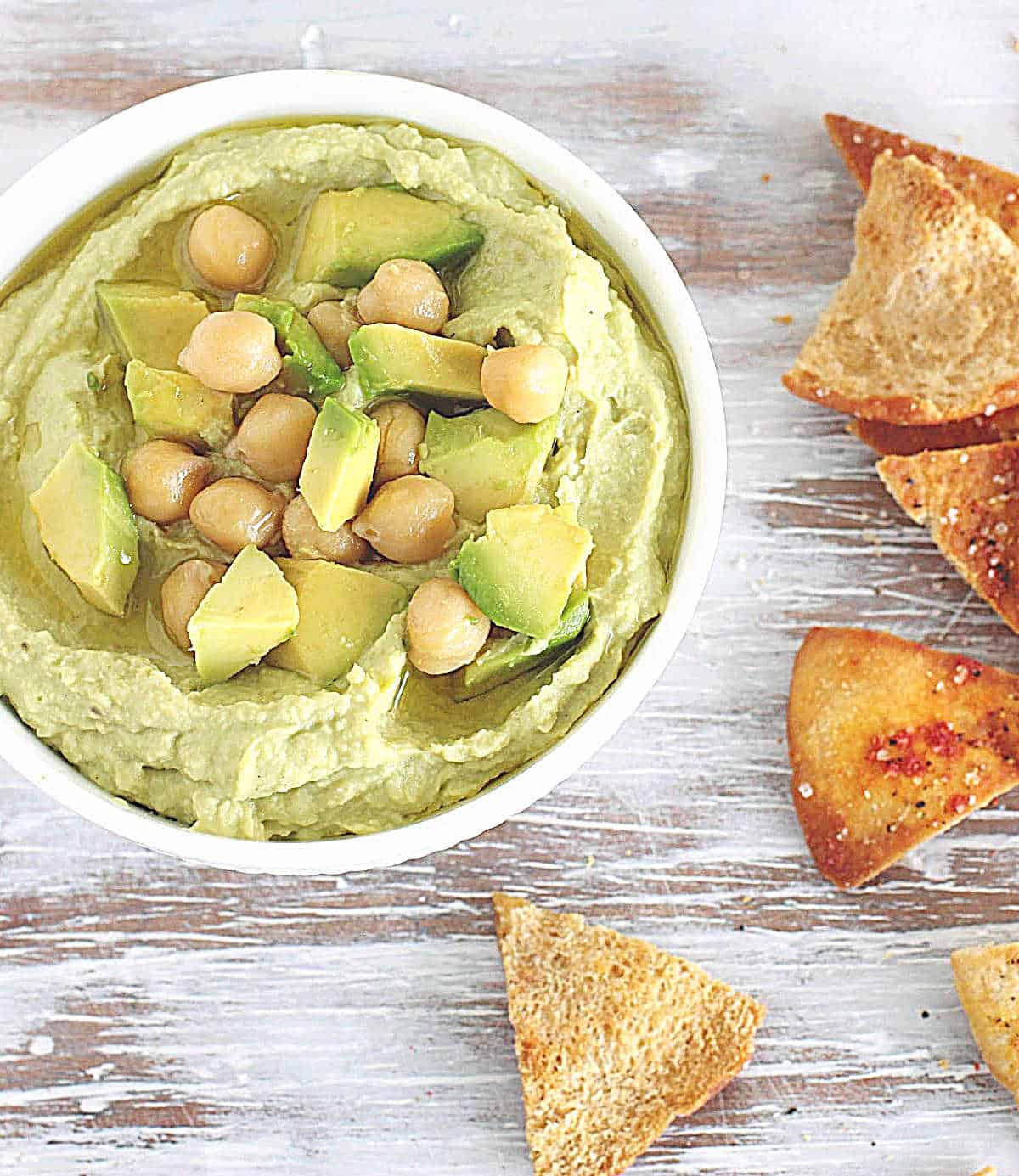White bowl with avocado dip, chickpeas and pita chips; on white wooden table
