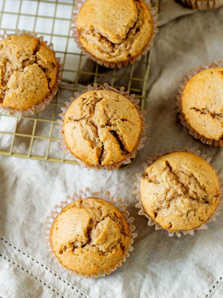 Several baked muffins on wire rack over grey napkin