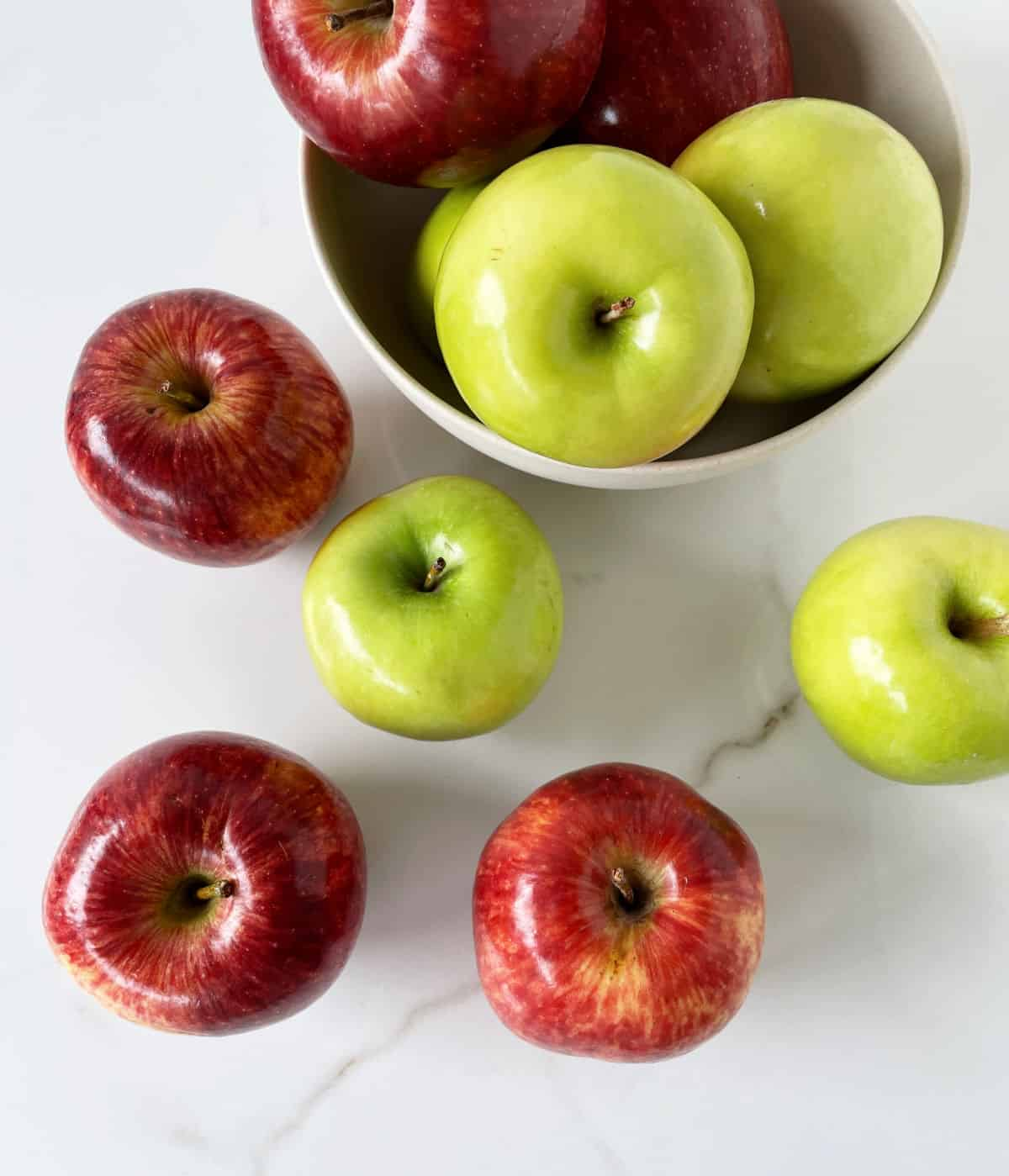 Green and red apples in bowl on white marble