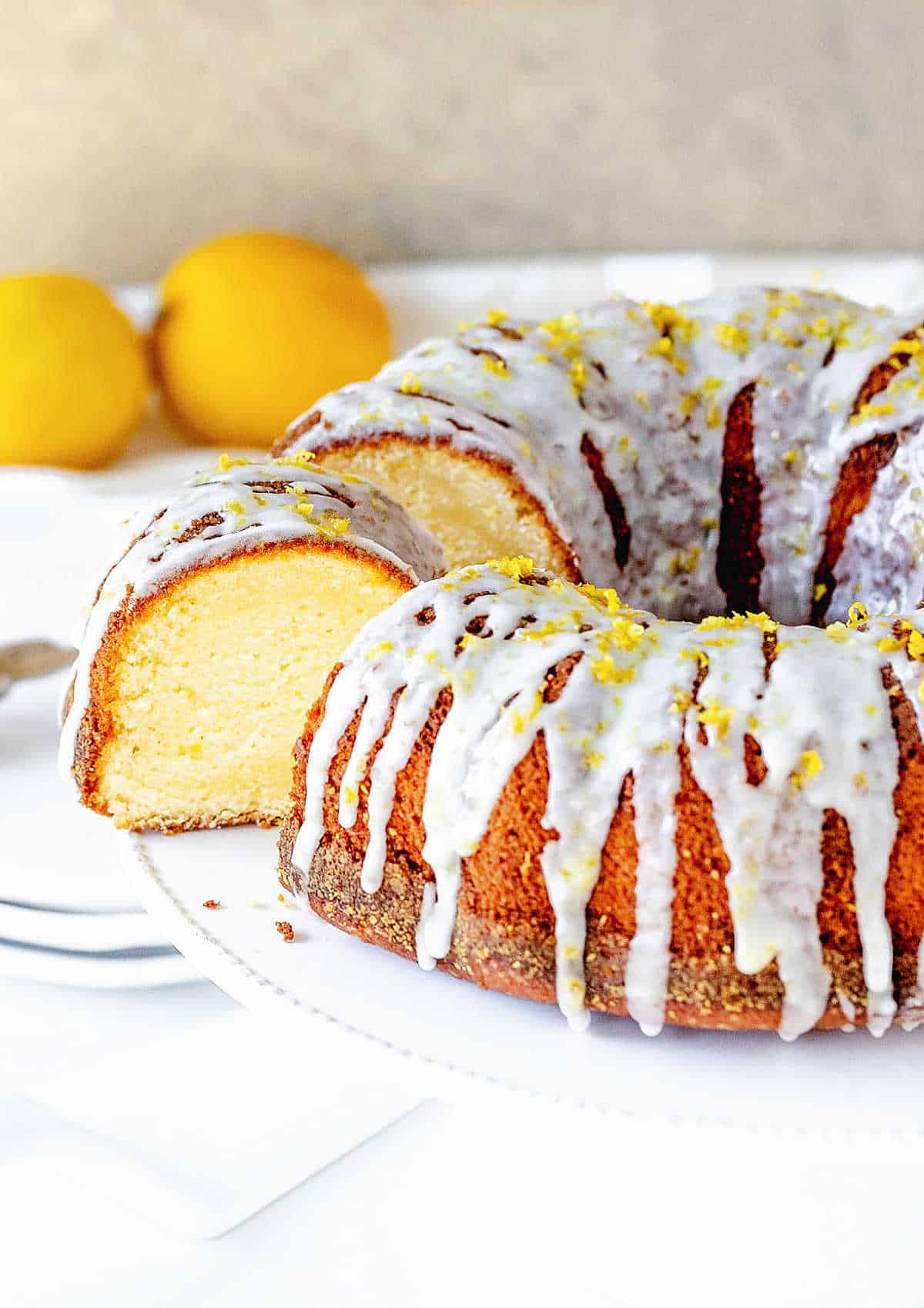 Glazed lemon bundt cake with cut slice, whole lemons, white beige background