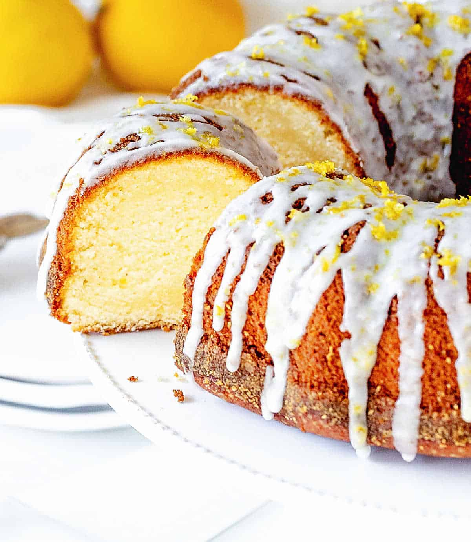 A slice of lemon bundt cake cut from cake in white stand, lemons in background