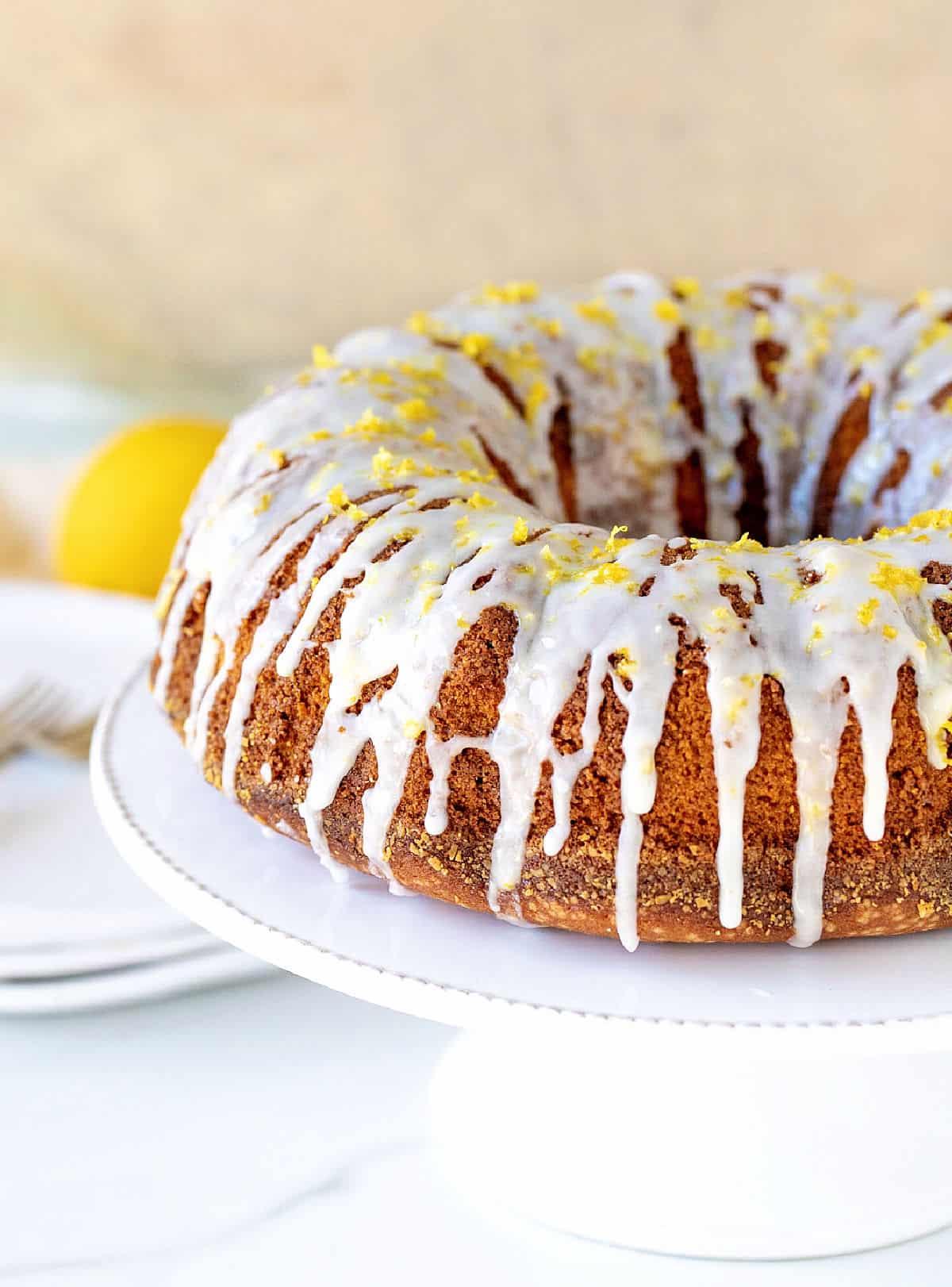 Partial view of glazed lemon bundt cake on white cake stand, beige background