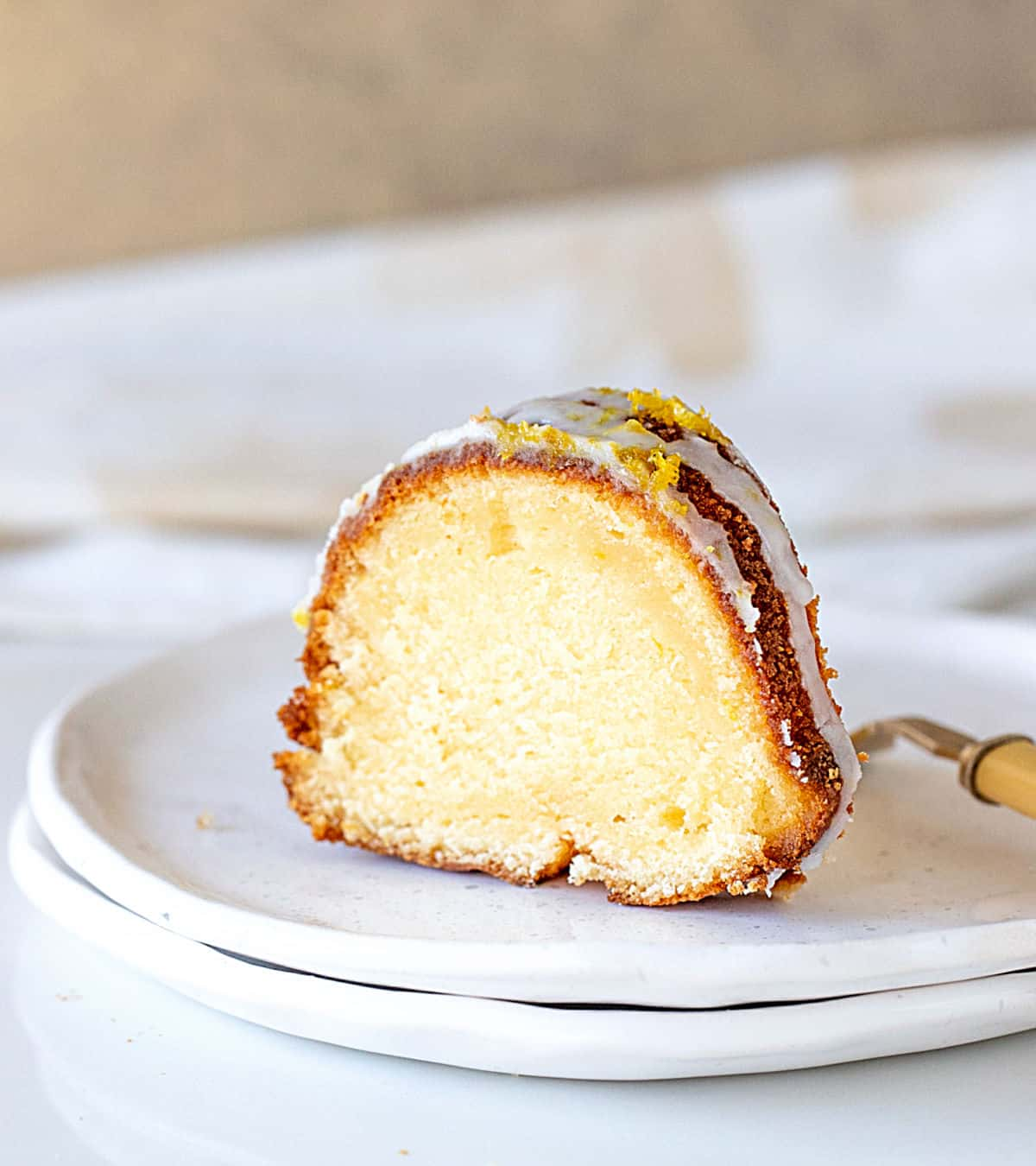 Single slice of lemon bundt cake on stack of white plates