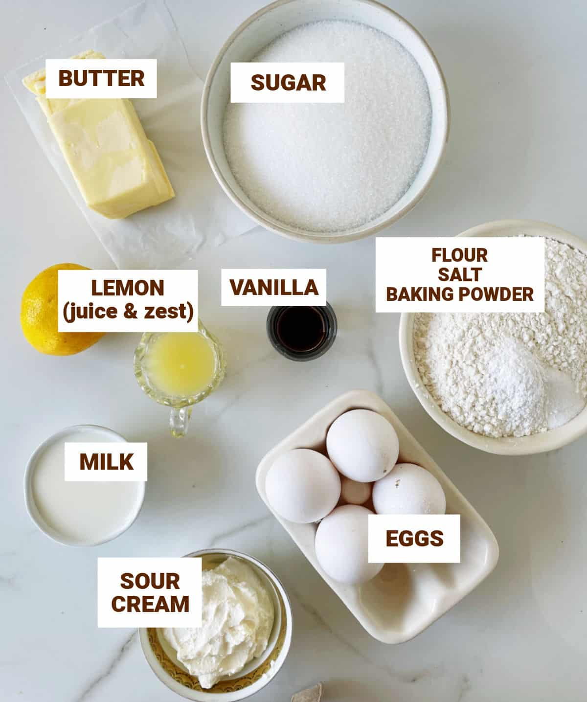 White surface with bowls containing ingredients for lemon cake including butter, eggs, sour cream, vanilla, milk