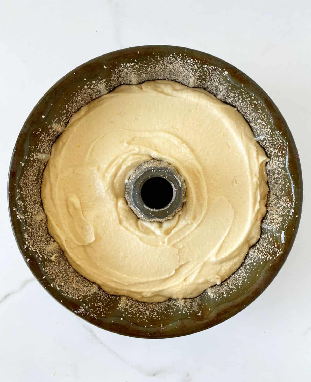 Bundt cake batter in dark metal pan on a white surface