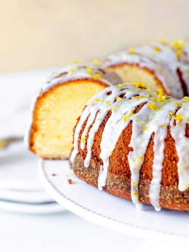 Lemon bundt cake with glaze and cut slice on white cake stand, beige background