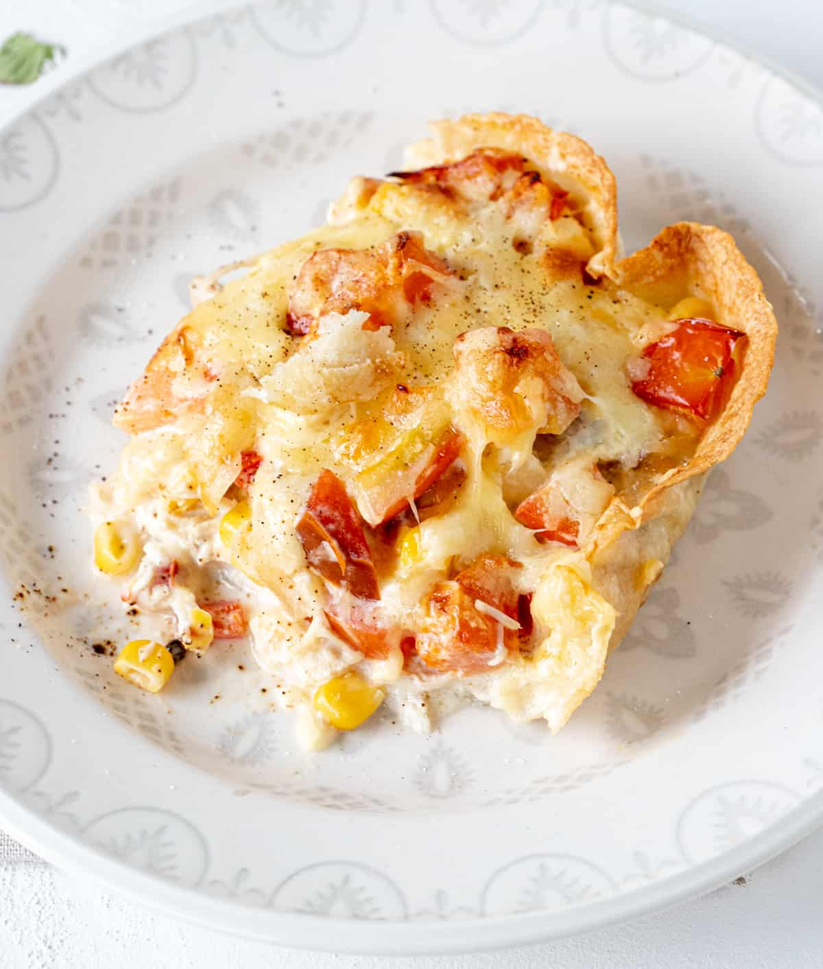 Top view of white plate with serving of chicken casserole with cheese, corn, and tomatoes.
