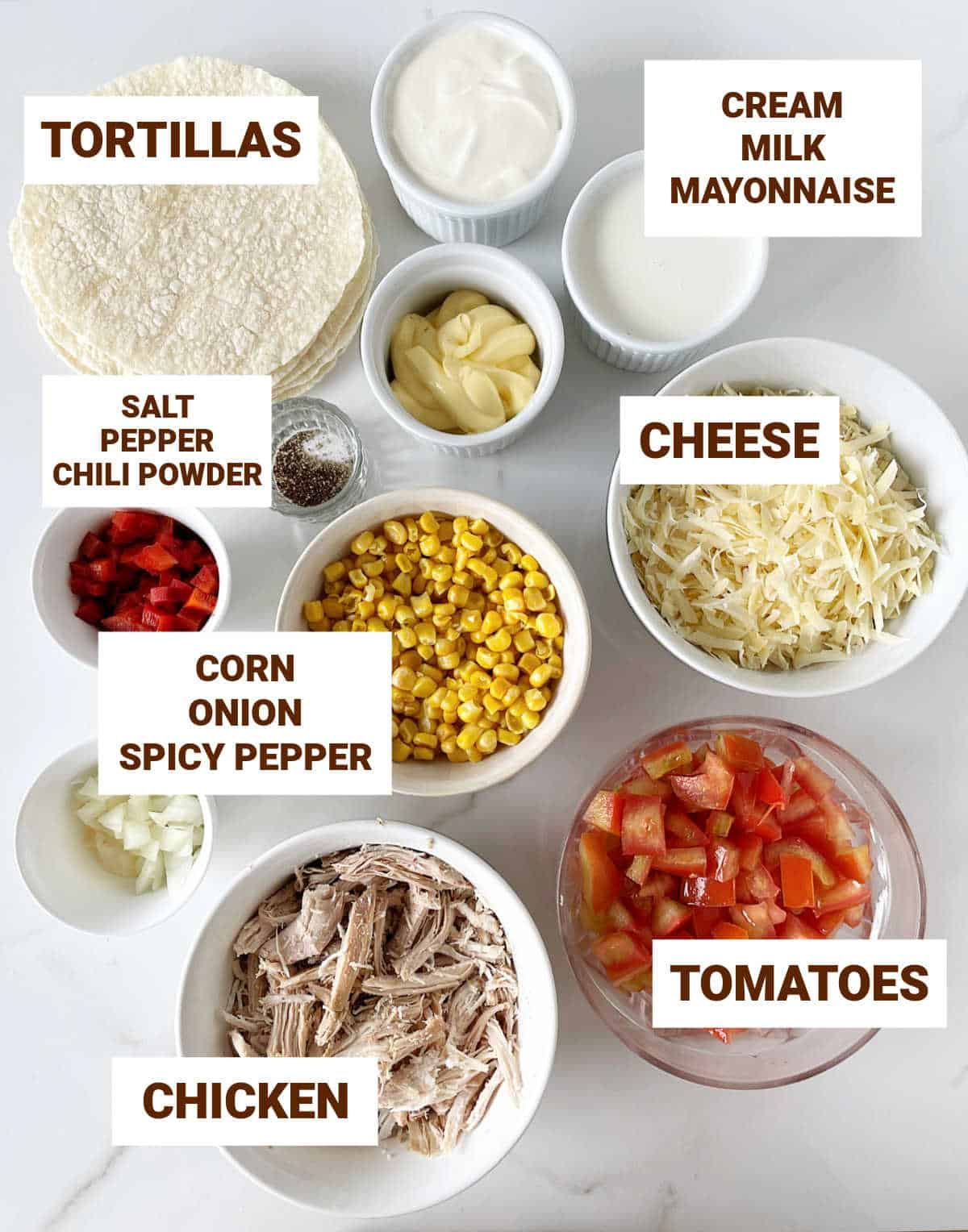 Bowls on white surface with ingredients for chicken corn casserole including tortillas, cheese, tomatoes, condiments