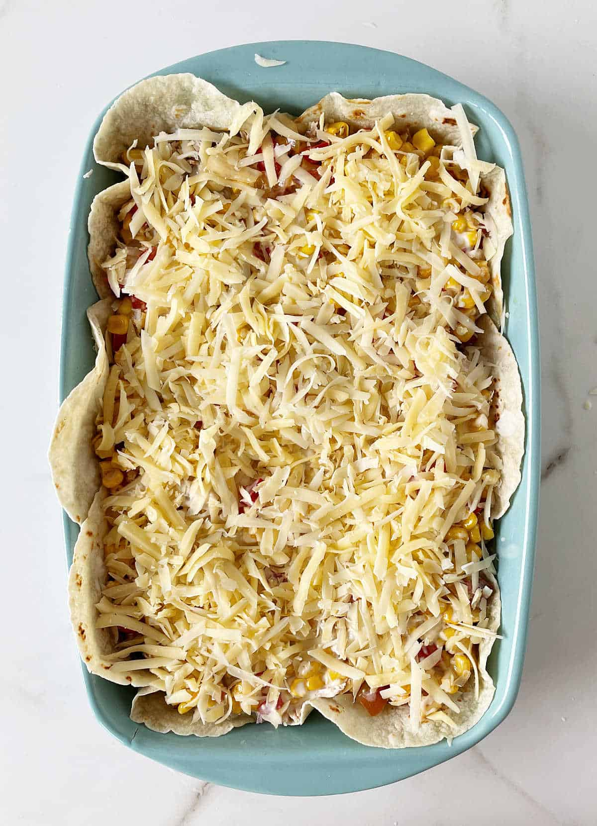 Cheese topped unbaked chicken casserole in blue dish on white surface