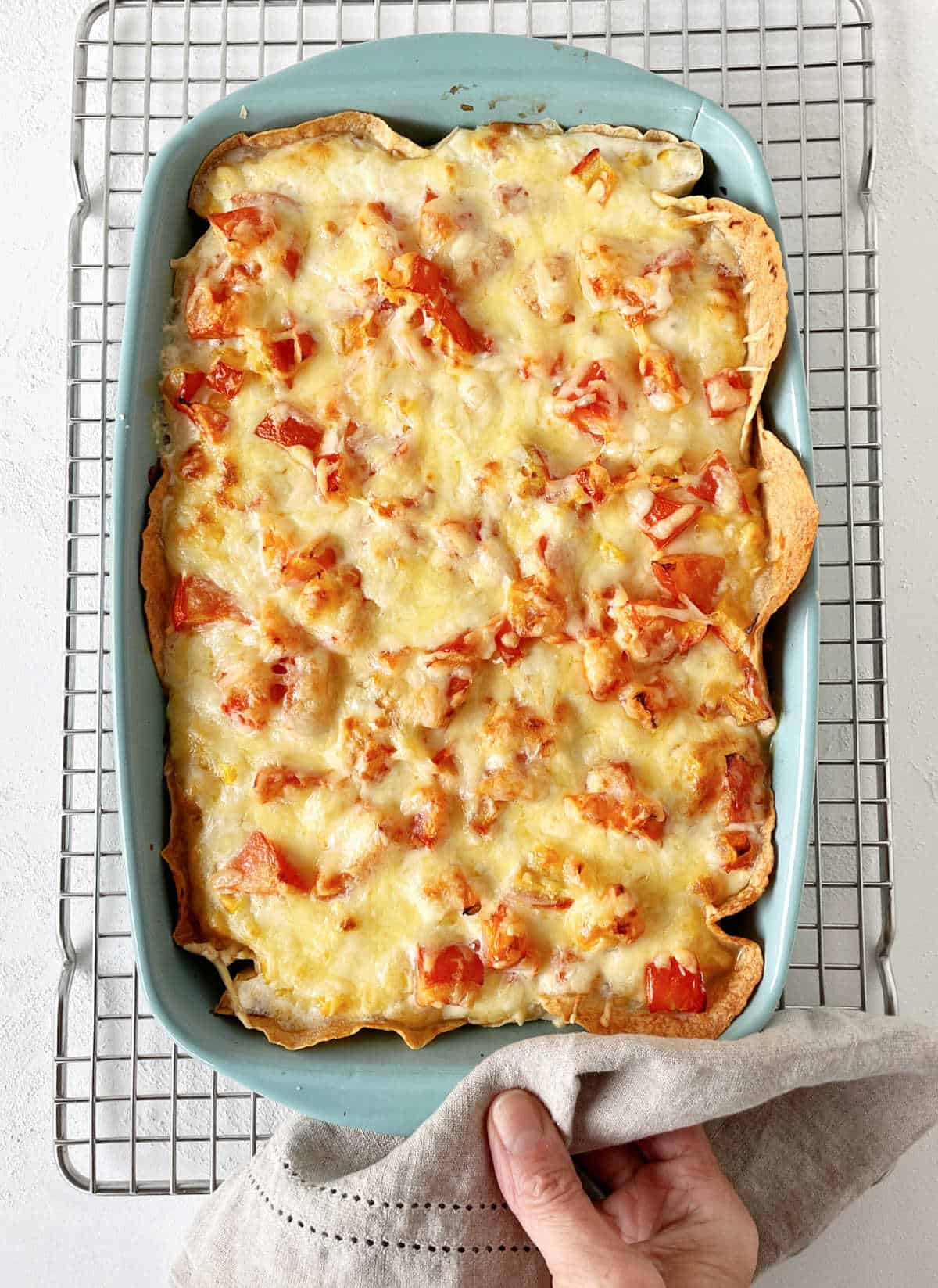Baked cheese and tomato topped casserole in blue dish on wire rack