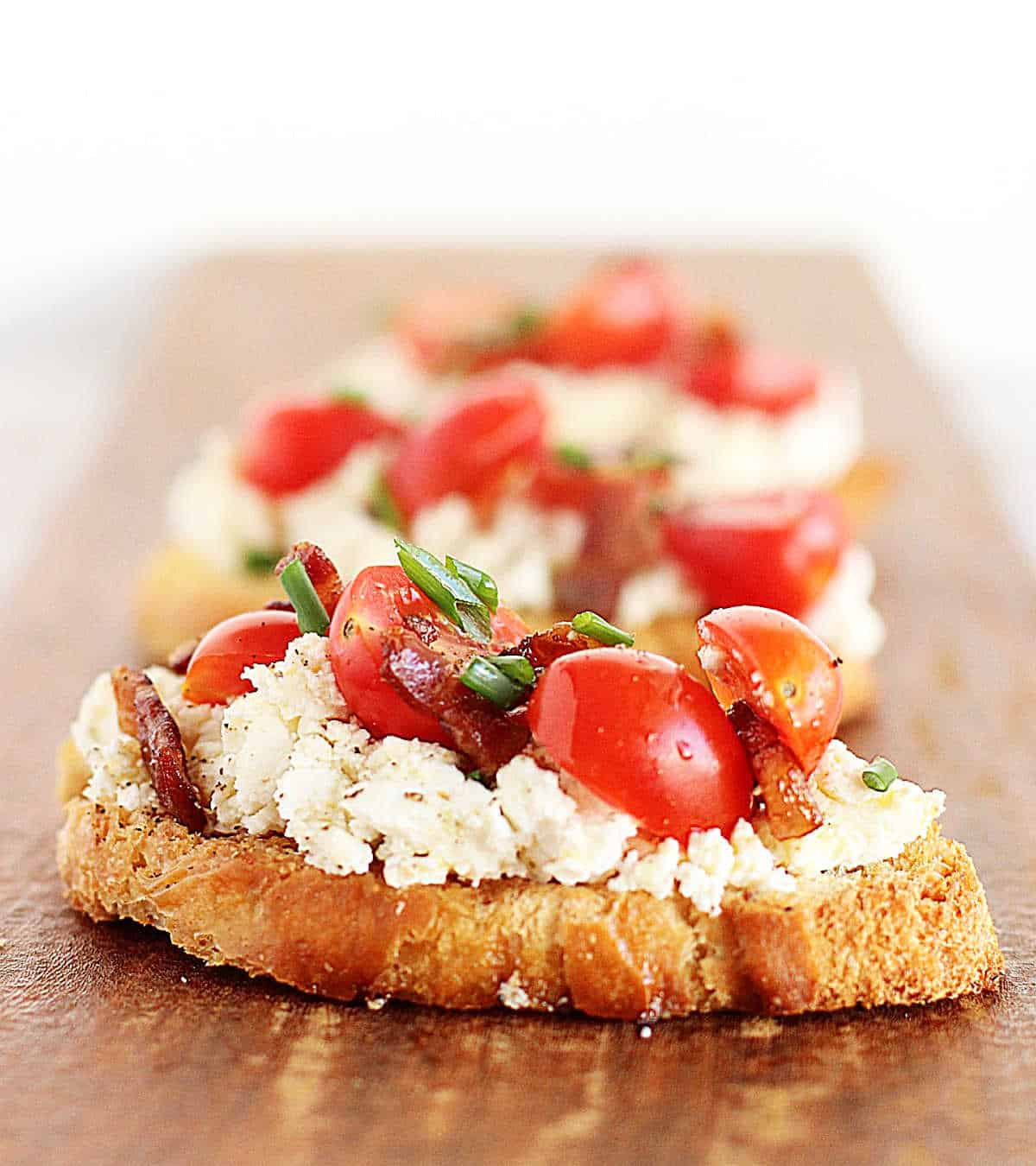 Long wooden board with row of ricotta tomato toast