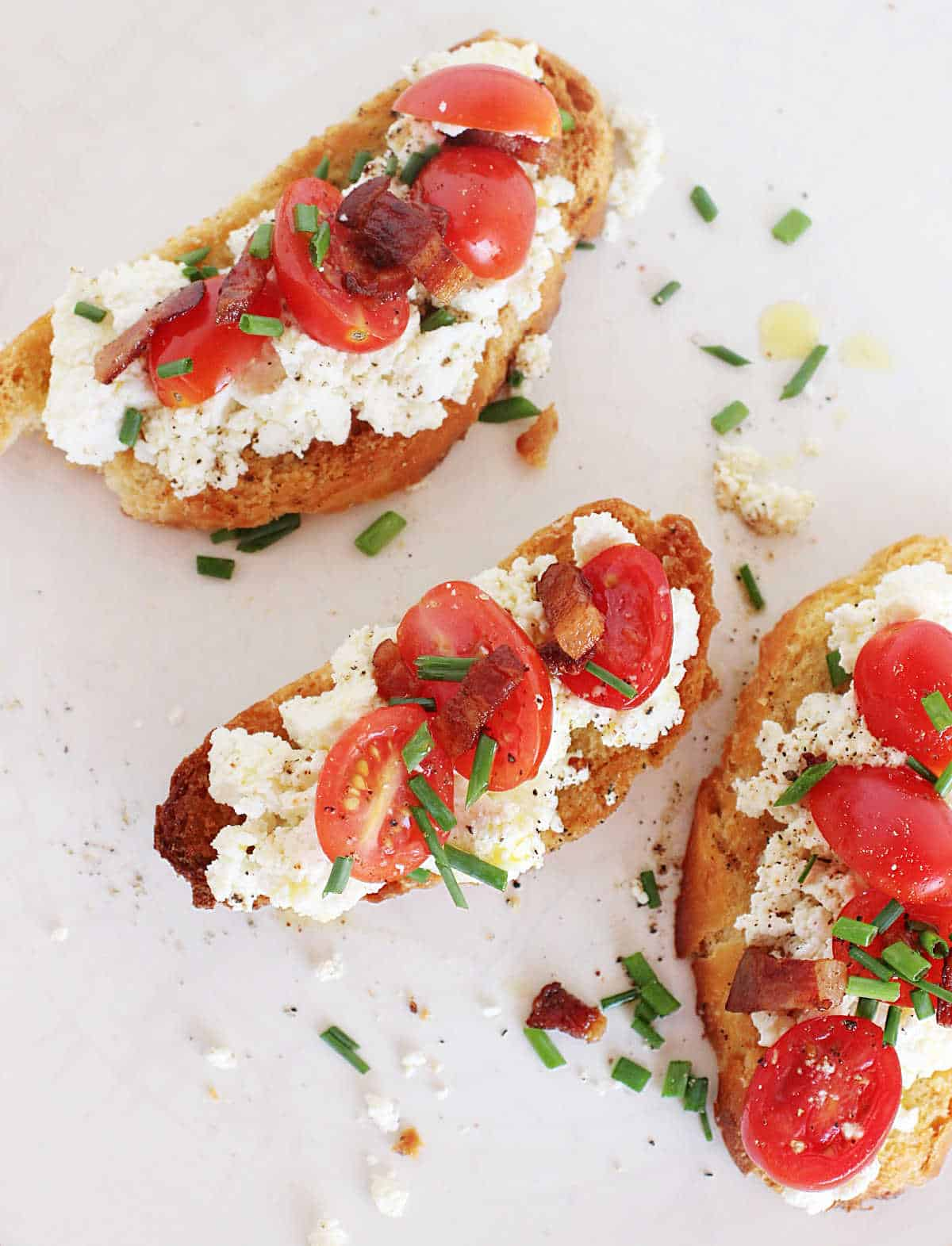 Top view of three ricotta tomato toasts on white plate