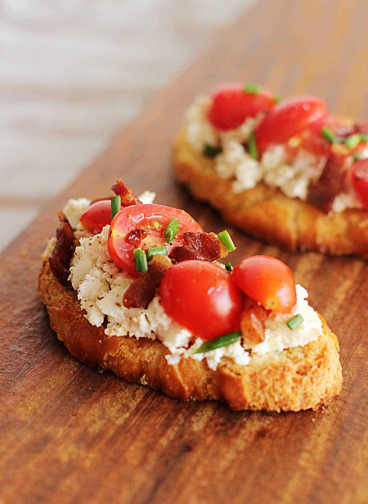 Two slices of ricotta toast wit tomatoes and bacon on wooden board