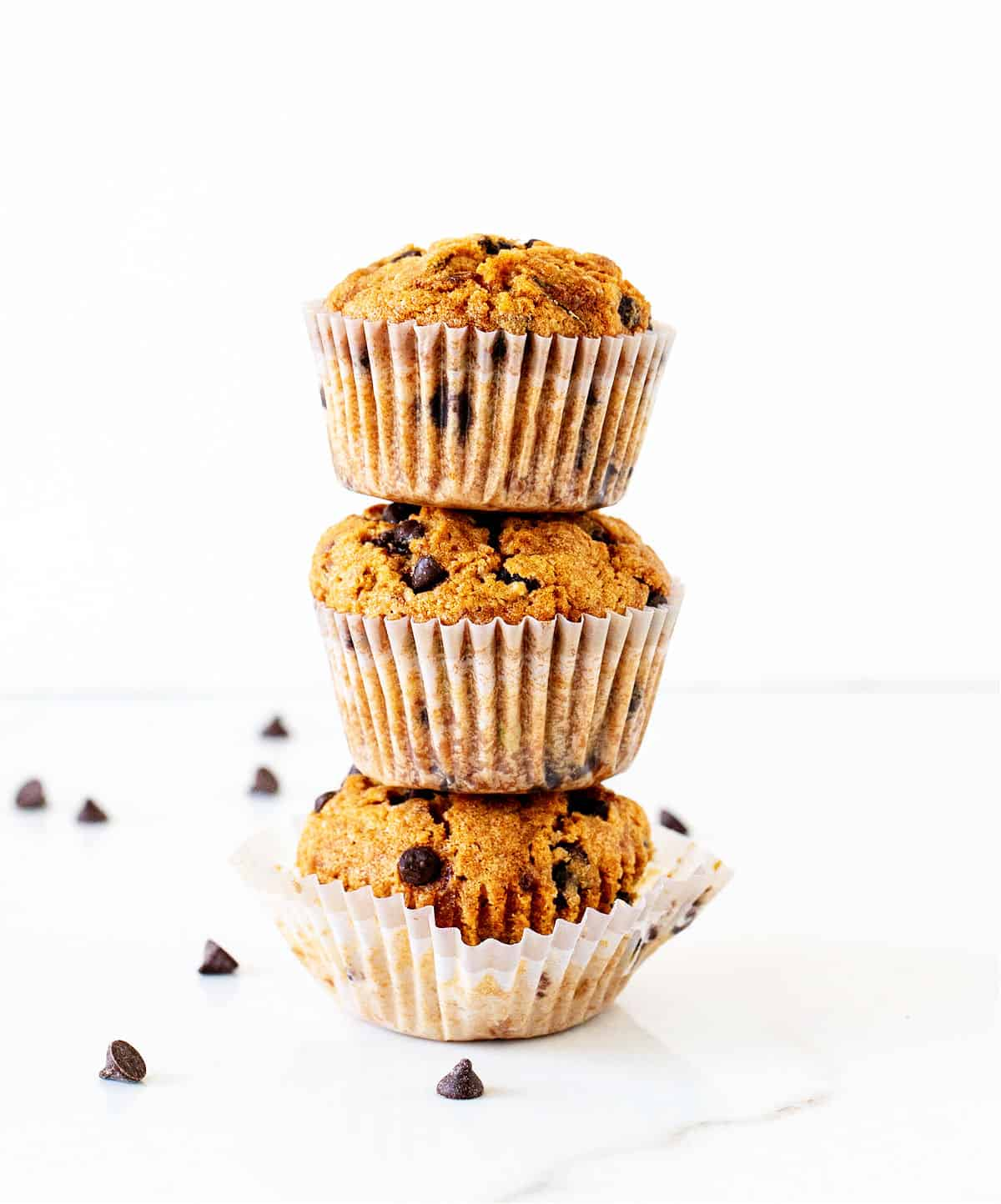 White background with stack of muffins with chocolate chips in paper liners