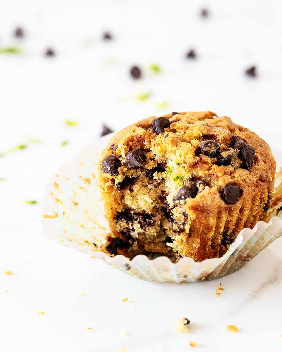 Bitten chocolate chip muffin on paper cup and white background