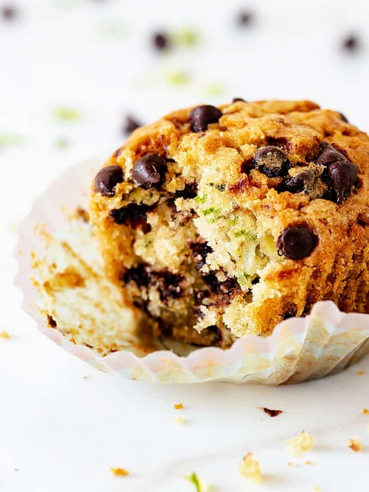 Close up of single bitten muffins with chocolate chips on white background