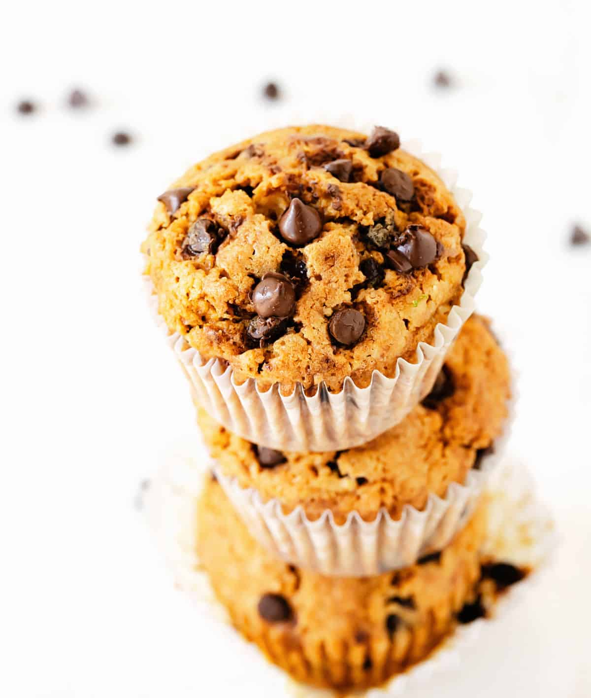 Top view of stacked chocolate chip muffins on paper liners, white background