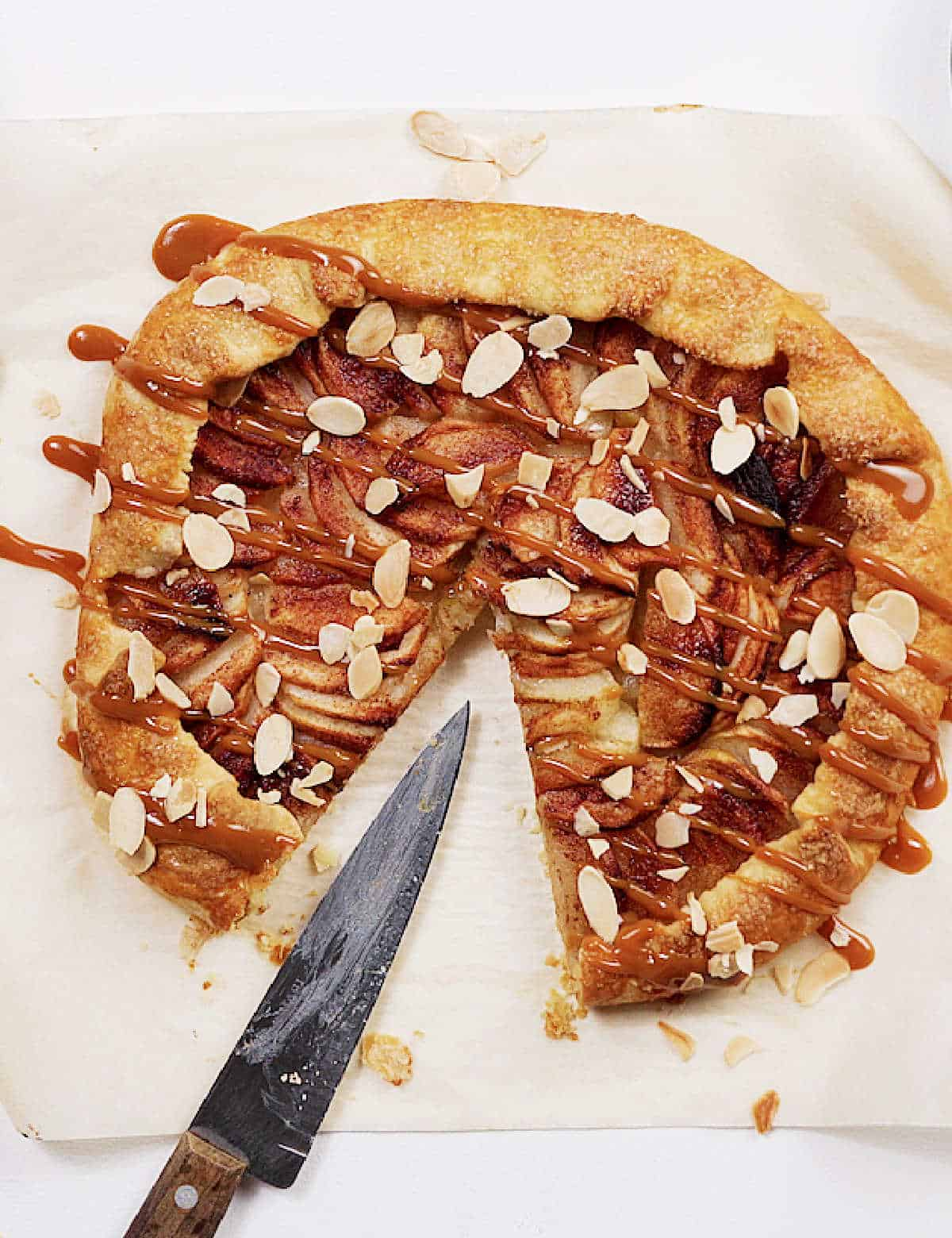 Top view of apple caramel galette with one missing slice, a knife, white surface
