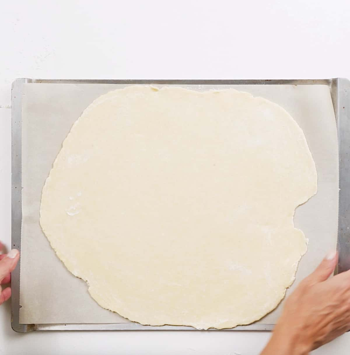 Flat round of rolled pie crust on parchment paper on metal baking sheet