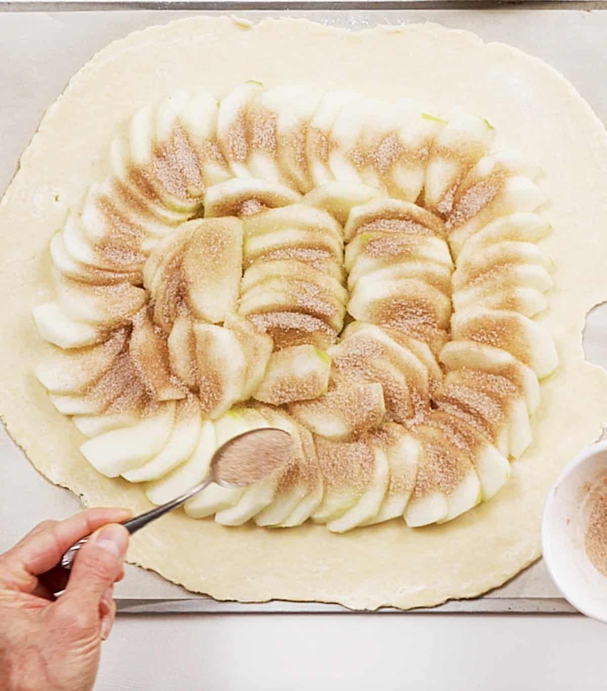 Sprinkling cinnamon sugar to apple slices on top of rolled pie crust