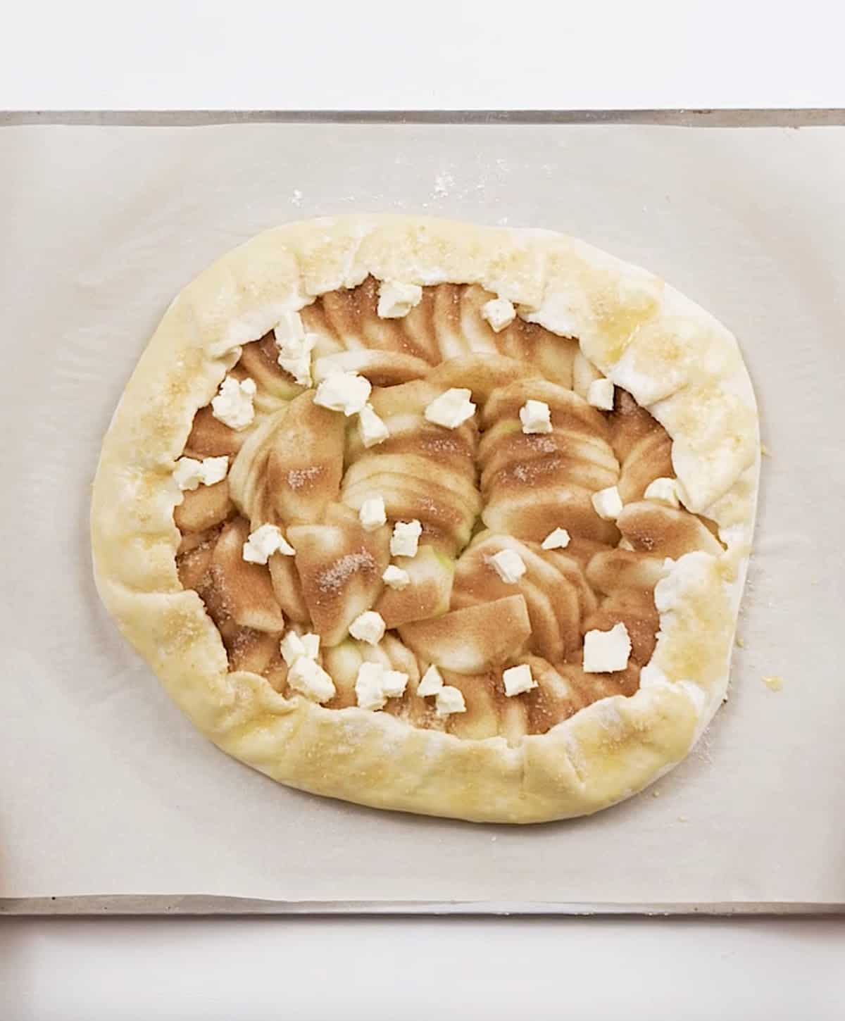 Whole unbaked apple galette on parchment paper