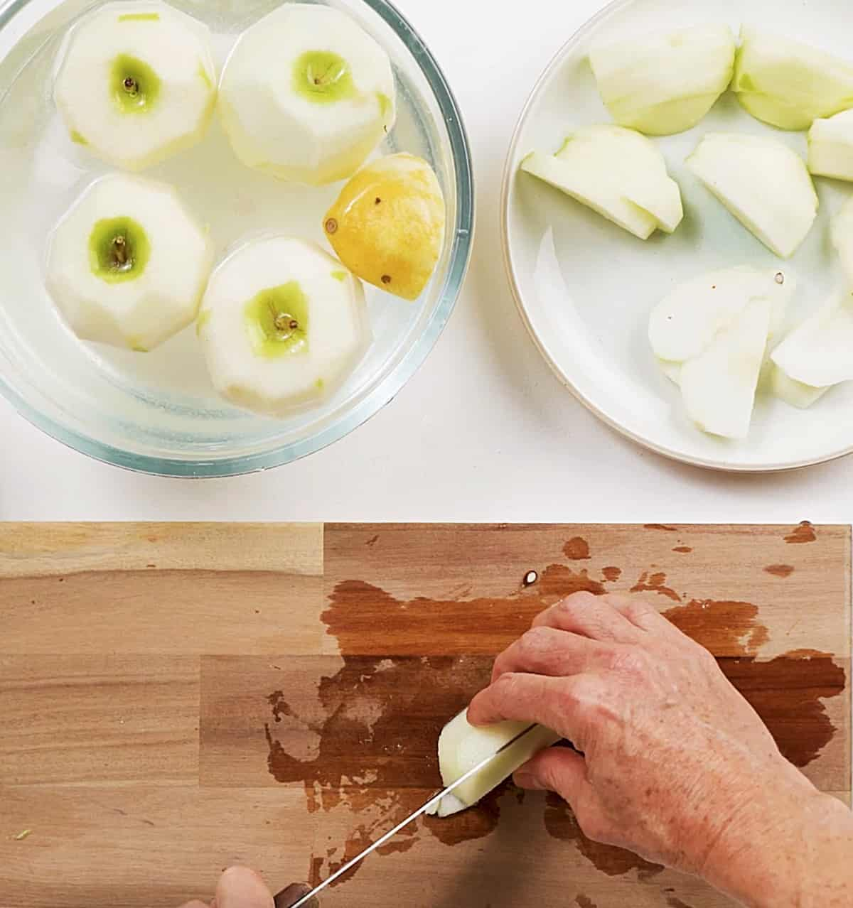 Cutting apples in wooden board with bowl containing peeled apples